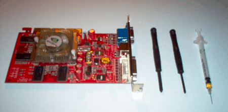 a video card next to two screwdrivers and a syringe